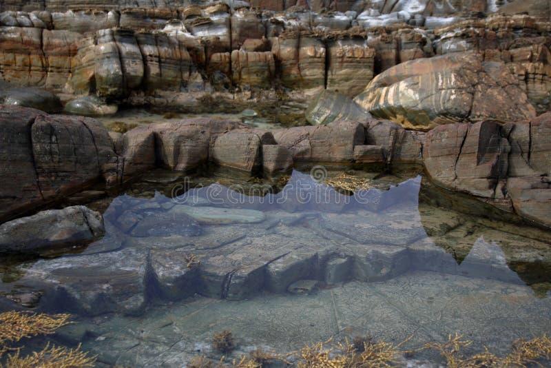 Ontruim weerspiegelende watervulklei in de oceaanrotsen, op afgelegen Arthur Pieman Conservation-gebied, de Westkust van Tasmanig stock foto's