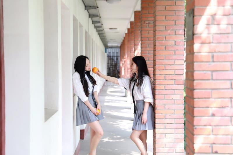 Ontspan Aziatisch Chinees mooi de studentenkostuum van de meisjesslijtage in school genieten van vrije tijd eten fruitsinaasappel royalty-vrije stock afbeelding