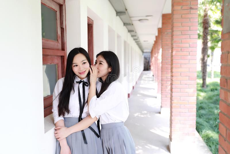 Ontspan Aziatisch Chinees mooi de studentenkostuum van de meisjesslijtage in school genieten vrije tijd van roddel in klaslokaal stock foto's
