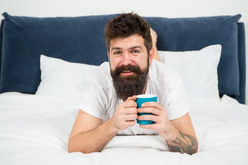 Ontspan en rust Hoogtepunt van energie De koffie be?nvloedt lichaam Mensen het knappe hipster ontspannen op bed met koffiekop geb royalty-vrije stock foto