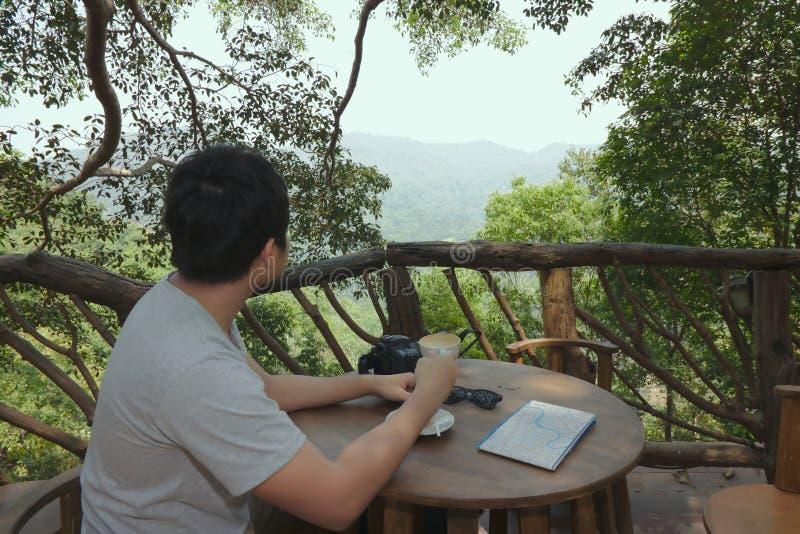 Ontspan tijd van gelukkige jonge Aziatische de koffie van de mensenholding kop en het bekijken mooie aard stock fotografie
