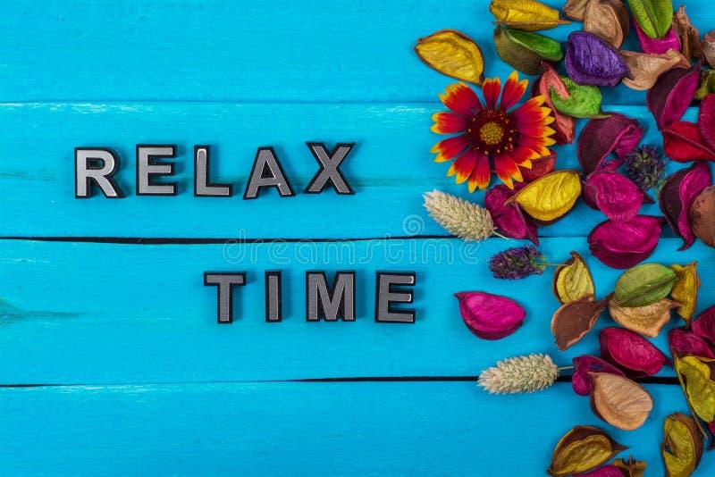 Ontspan tijdtekst op blauw hout met bloem stock afbeelding