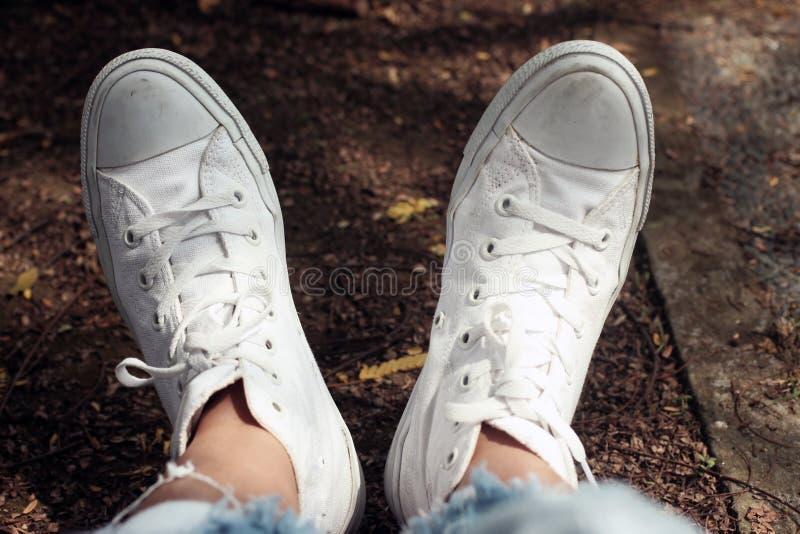 Ontspan voeten van jonge vrouw op witte tennisschoenenachtergrond Inspiratiesconcept met exemplaarruimte Menselijk lichaamsdeel i royalty-vrije stock fotografie