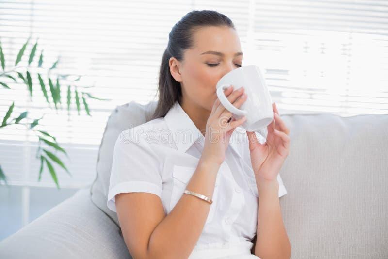 Ontspannen aantrekkelijke vrouw het drinken koffie royalty-vrije stock fotografie