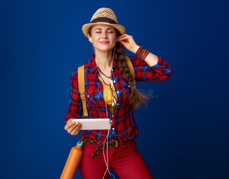 Ontspannen actieve vrouwenwandelaar die met tabletpc aan muziek luisteren stock afbeeldingen