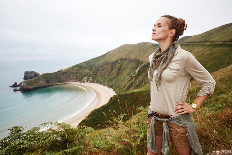 Ontspannen actieve vrouwenwandelaar voor oceaanmeningslandschap stock afbeelding