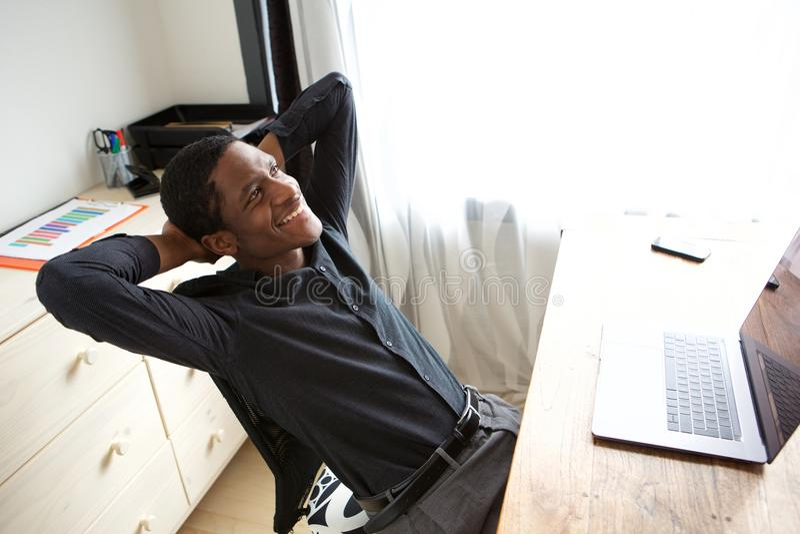 Ontspannen Afrikaanse Amerikaanse zakenmanzitting bij bureau met handen achter hoofd royalty-vrije stock foto's