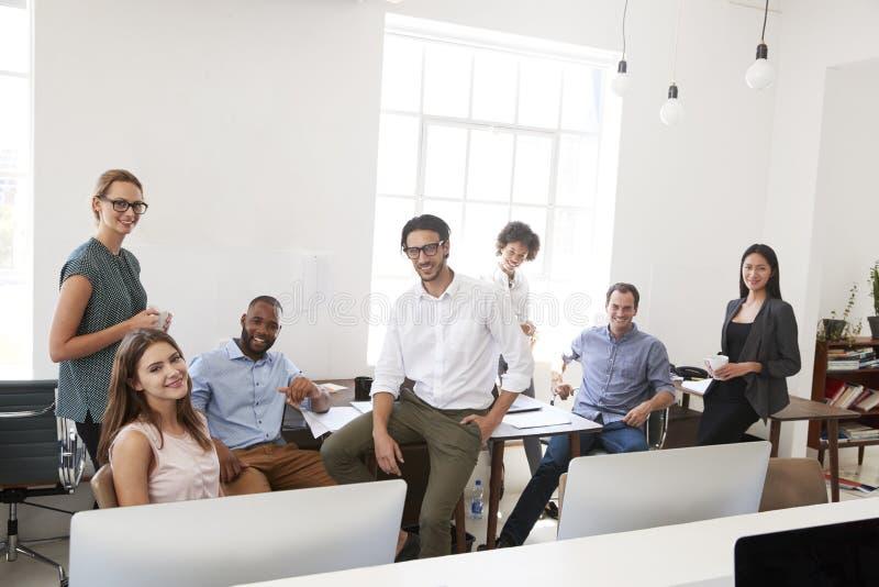 Ontspannen bedrijfscollega's in hun bureauglimlach aan camera royalty-vrije stock fotografie