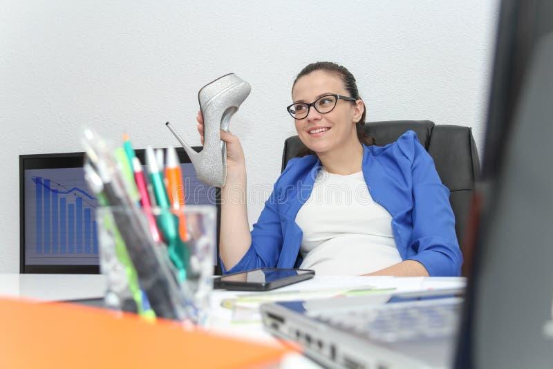 Ontspannen en het winnen bedrijfsvrouwenzitting met haar benen op bureau stock foto