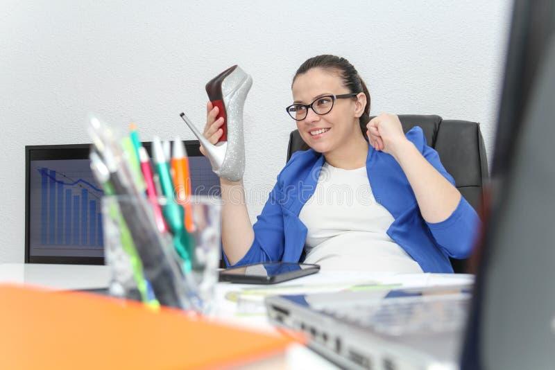 Ontspannen en het winnen bedrijfsvrouwenzitting met haar benen op bureau royalty-vrije stock foto's