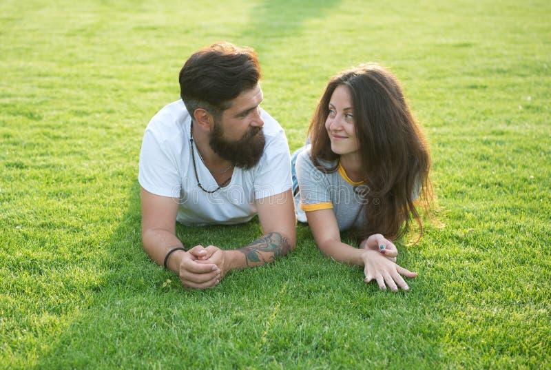 Ontspannen en in liefde Paar het ontspannen op gras die van elkaar genieten Man gebaarde hipster en mooie vrouw in liefde De zome royalty-vrije stock afbeeldingen