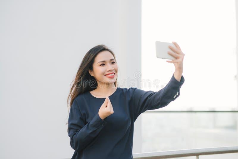 Ontspannen en vrolijk Het werk en vakantie Openluchtportret van gelukkige jonge vrouw gebruikend smartphone, doend selfie foto en royalty-vrije stock foto