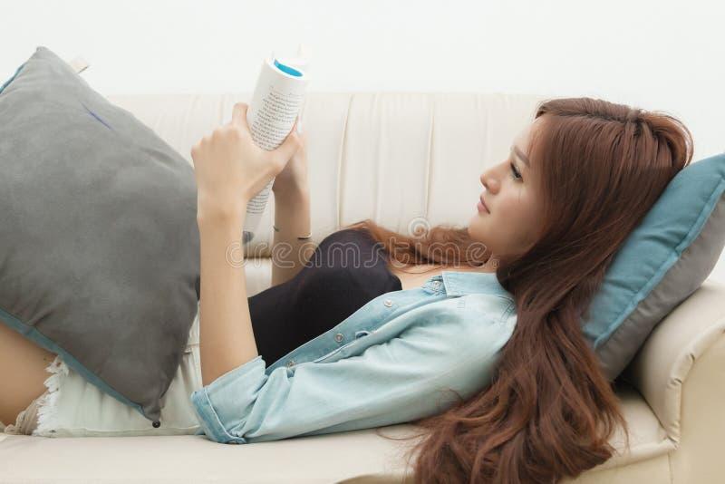 Ontspannen gelukkige vrouw die een boek in een zitting van de ebooklezer op een laag thuis lezen stock afbeelding