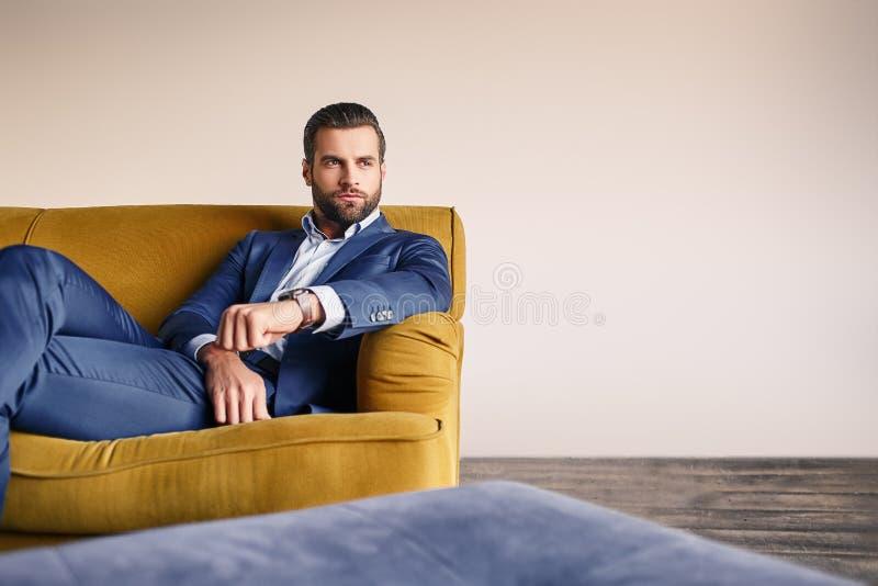 Ontspannen gevoel De knappe en goed-geklede zakenman rust op bank en denkt over zaken stock foto's