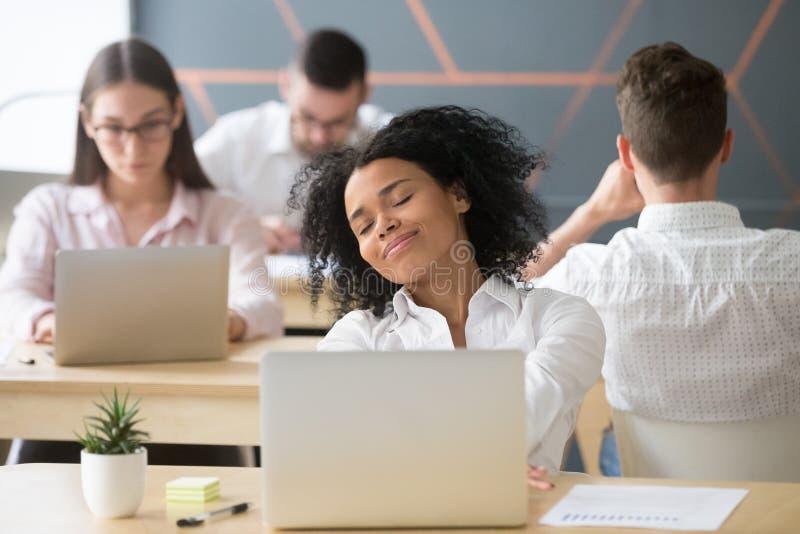 Ontspannen glimlachende Afrikaanse vrouw die van onderbreking in het coworking genieten, geen st stock foto