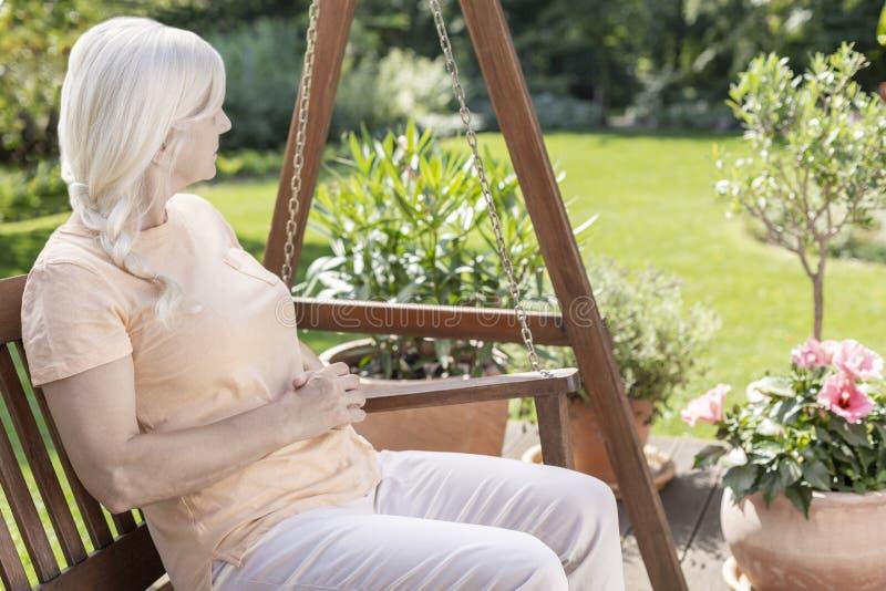 Ontspannen hogere vrouw bij het hangen van stoel in de tuin tijdens de zomer royalty-vrije stock afbeelding