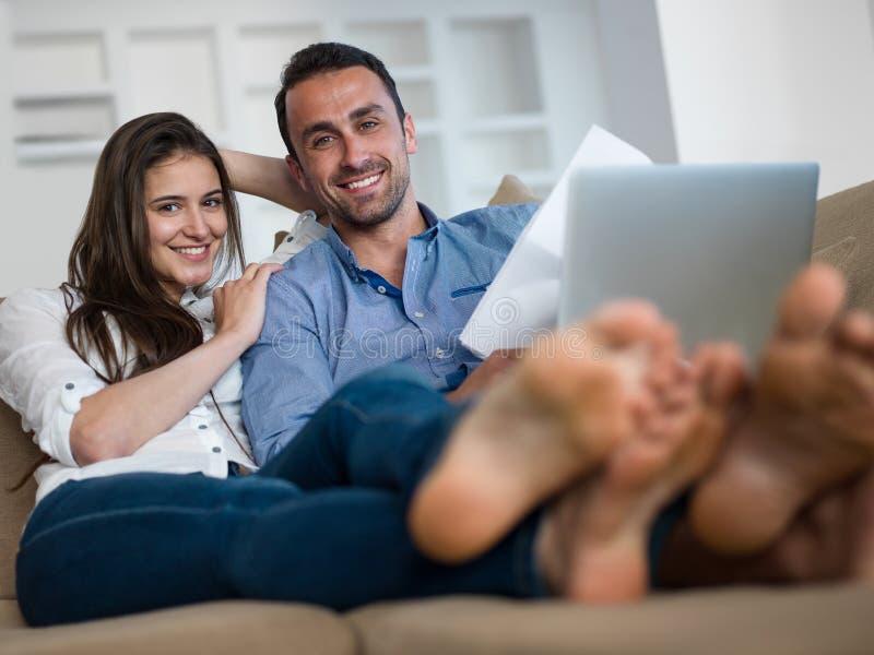 Ontspannen jong paar die aan laptop computer thuis werken stock afbeelding