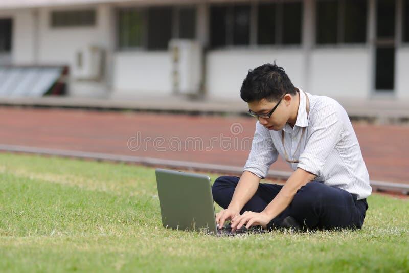 Ontspannen jonge Aziatische bedrijfsmens die met laptop aan groen gras werken stock foto