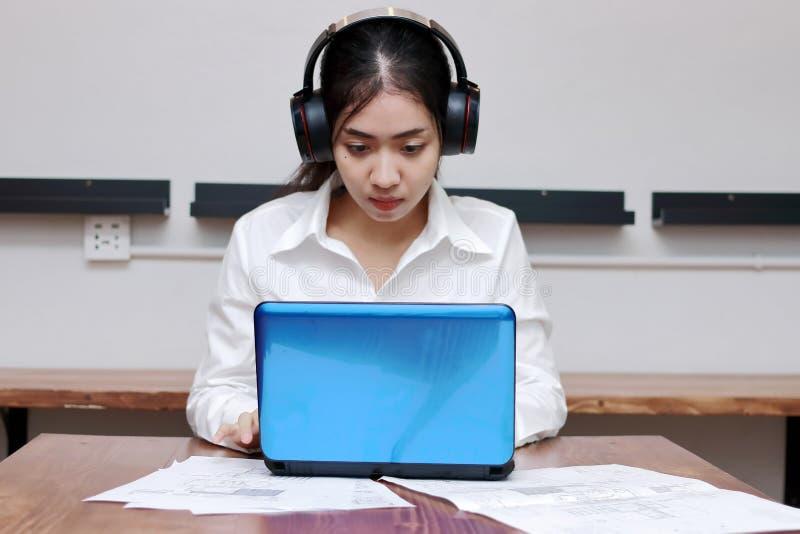 Ontspannen jonge Aziatische bedrijfsvrouw met hoofdtelefoons die met laptop in bureau werken royalty-vrije stock foto