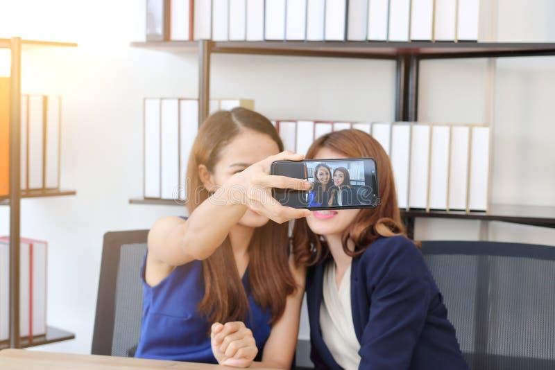 Ontspannen jonge Aziatische bedrijfsvrouwen die een beeld of selfie samen in bureau met zonneschijneffect nemen stock foto's