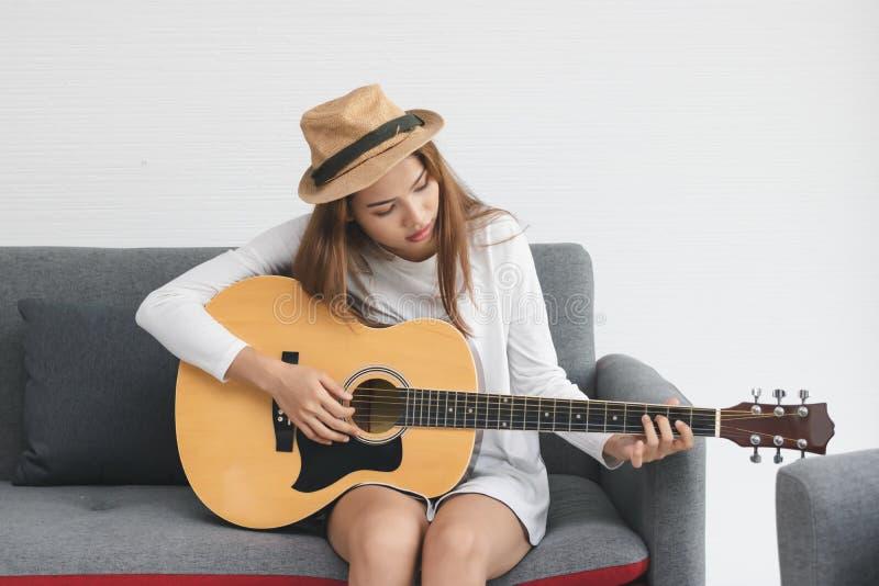 Ontspannen jonge Aziatische vrouw die akoestische gitaar in woonkamer spelen stock foto