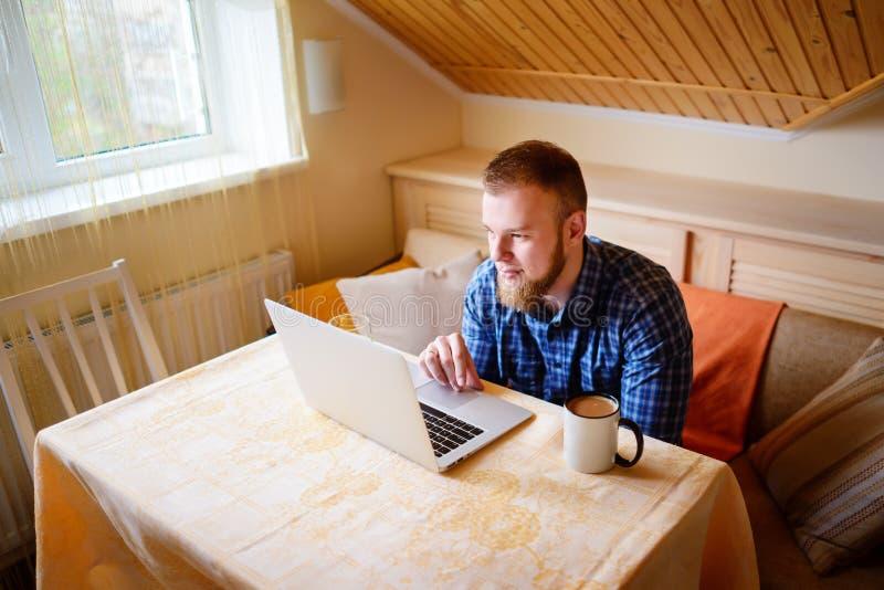 Ontspannen jonge beroeps die Internet op zijn laptop binnen surfen royalty-vrije stock afbeeldingen