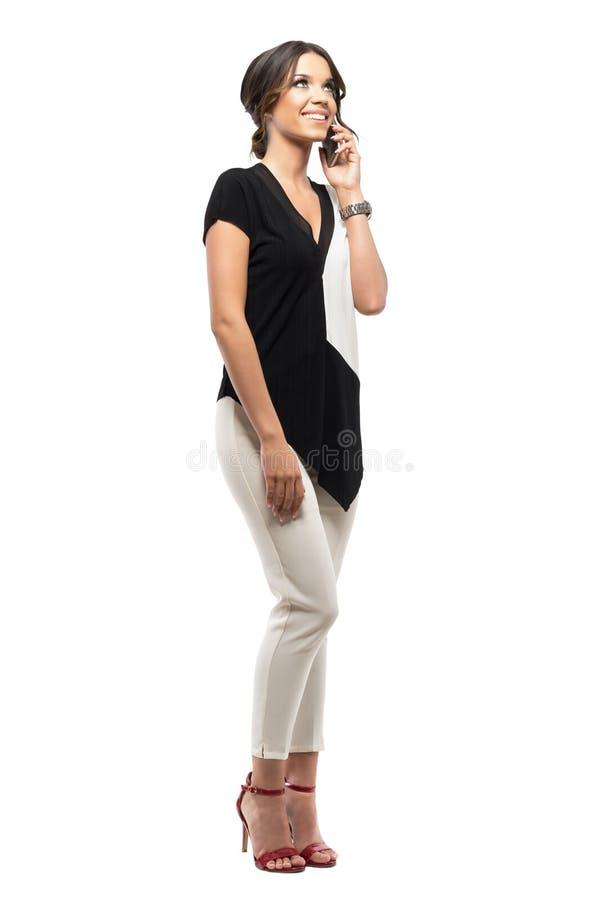 Ontspannen jonge elegante bedrijfsvrouw die op de en telefoon spreken die omhoog glimlachen eruit zien royalty-vrije stock foto's