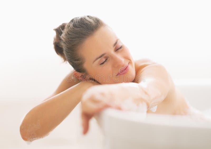 Ontspannen jonge vrouw in badkuip stock afbeeldingen