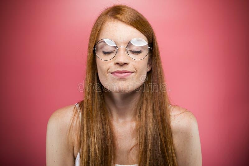 Ontspannen jonge vrouw die haar ogen sluiten terwijl het ontspannen over roze achtergrond royalty-vrije stock foto's
