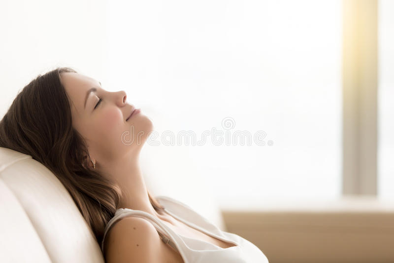 Ontspannen jonge vrouw die van rust op comfortabele bank, exemplaar genieten spac stock afbeelding