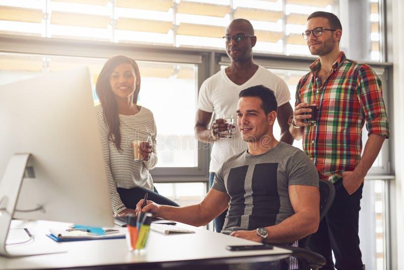 Ontspannen jonge werknemers rond computer in bureau royalty-vrije stock foto's