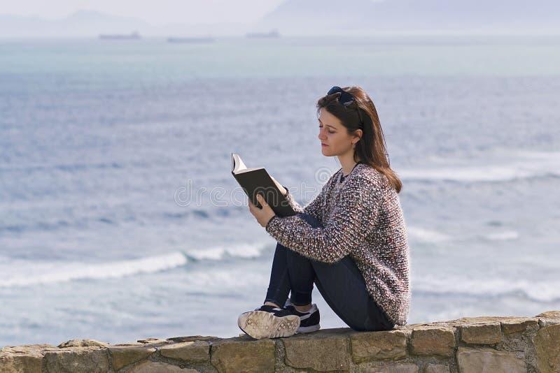 Ontspannen lezend een boek stock afbeeldingen