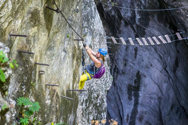 Ontspannen meisje beneden-beklimt a via ferratasectie over een route riep Postalmklamm, in Postalm-kloof, Boven-Oostenrijk royalty-vrije stock afbeelding