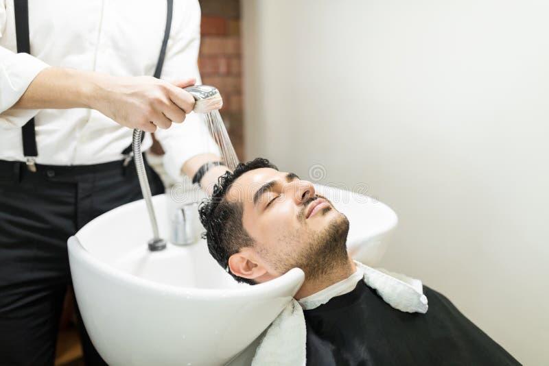 Ontspannen Mens die op Gootsteen leunen terwijl Kapper Washing His Hair royalty-vrije stock fotografie