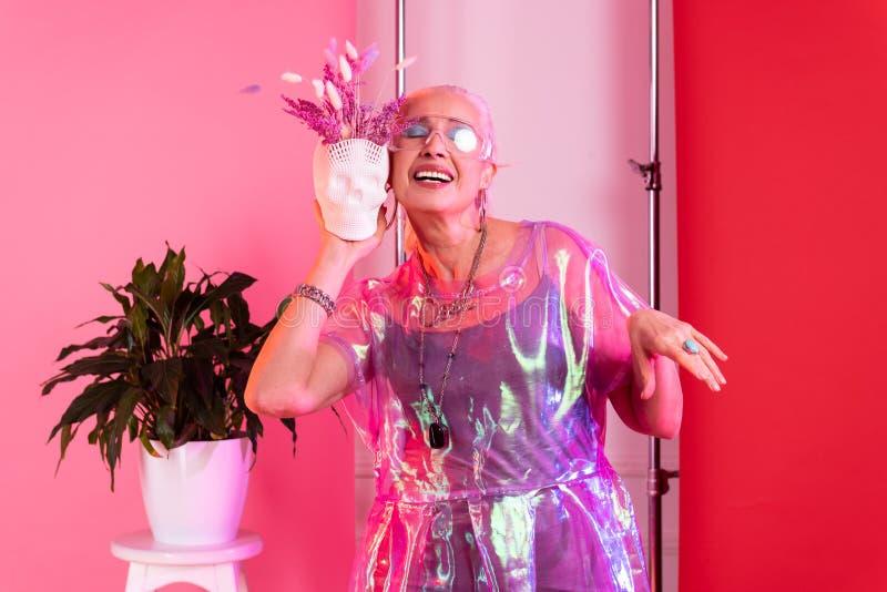 Ontspannen modieuze vrouw die haar oprechte glimlach aantonen royalty-vrije stock afbeelding