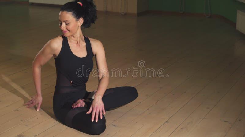 Ontspannen mooie gelukkige vrouw het praktizeren yoga in de avond thuis stock fotografie