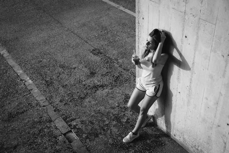 Ontspannen sportief jong vrouw het drinken detox sap en het rusten stock fotografie
