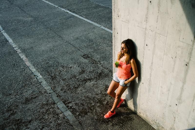 Ontspannen sportief jong vrouw het drinken detox sap en het rusten stock afbeeldingen