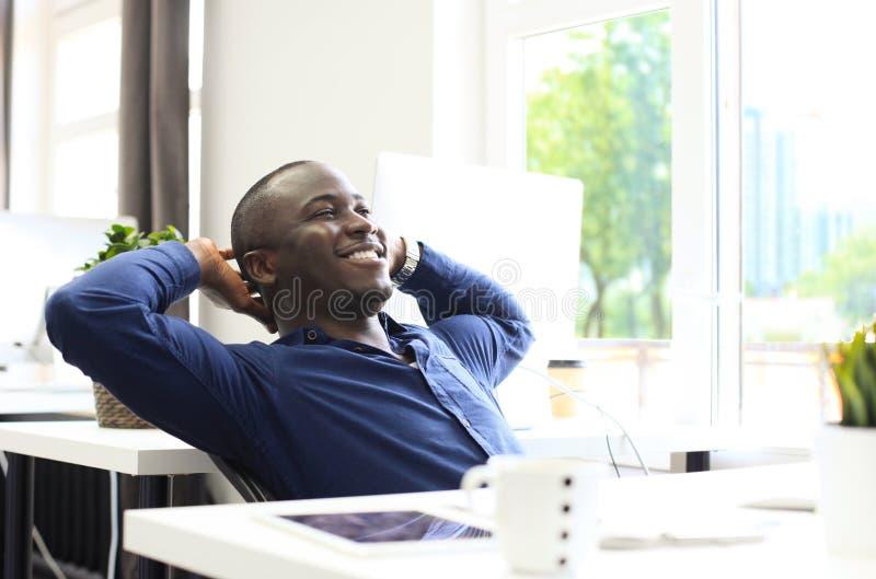 Ontspannen van Bedrijfs afro Amerikaanse mensenzitting bij zijn bureau die de lucht onderzoeken stock afbeelding