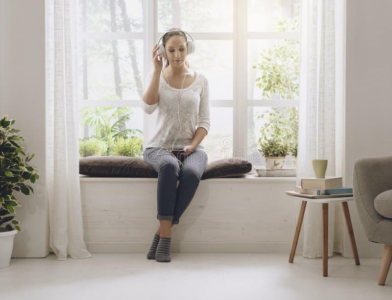 Ontspannen vrouw die aan muziek thuis luisteren stock fotografie