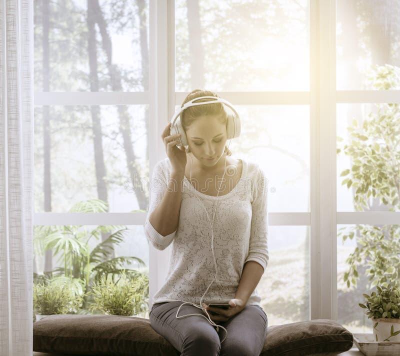 Ontspannen vrouw die aan muziek thuis luisteren stock afbeelding