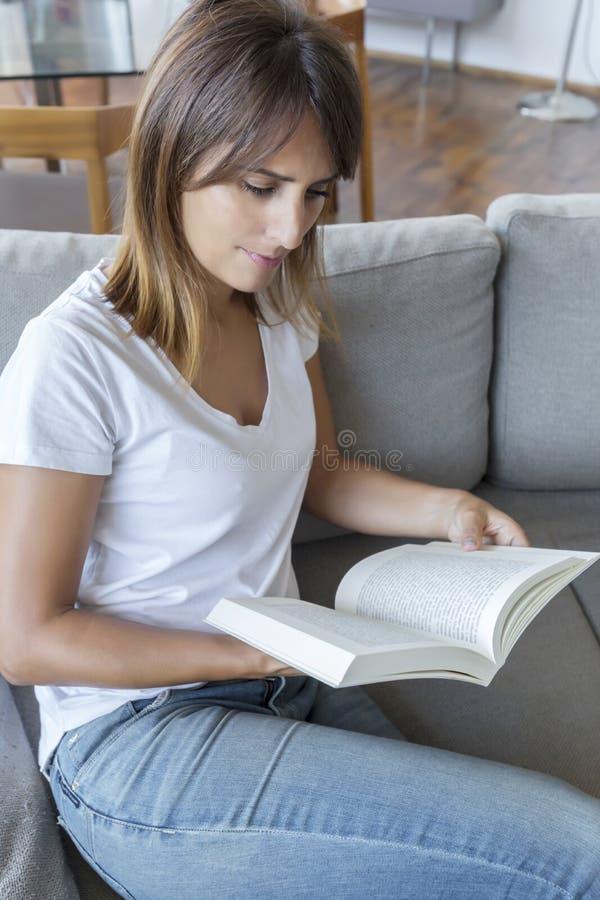 Ontspannen vrouw die een boek lezen terwijl thuis het zitten op een laag stock afbeelding