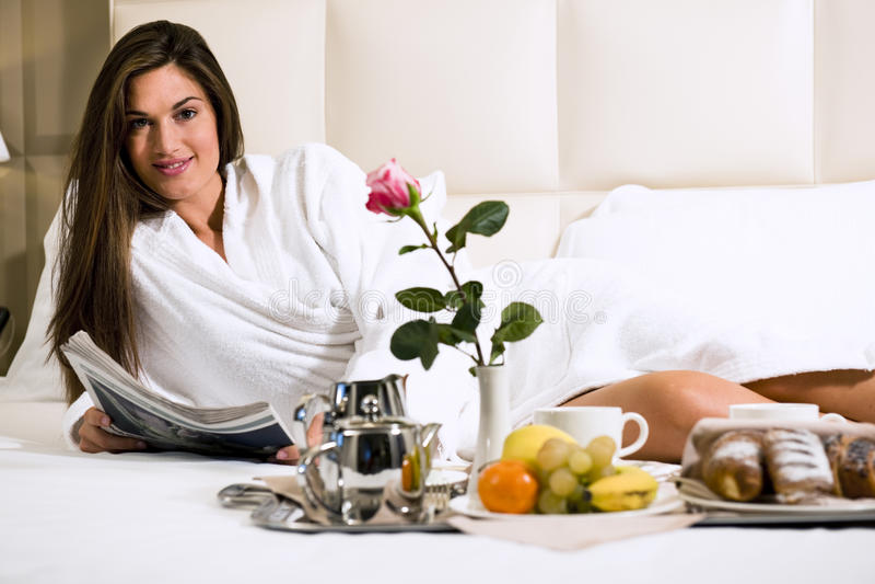 Ontspannen Vrouw die Ontbijt in Bed heeft stock afbeeldingen