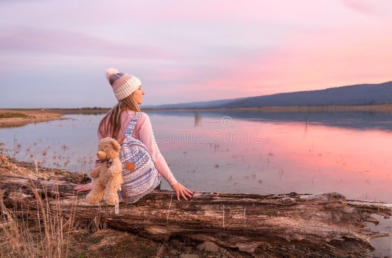 Ontspannen vrouw die op een rustige zonsondergang letten door het meer stock foto