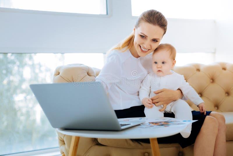 Ontspannen vrouw die op laptop richten terwijl het onderhouden van een baby stock afbeeldingen