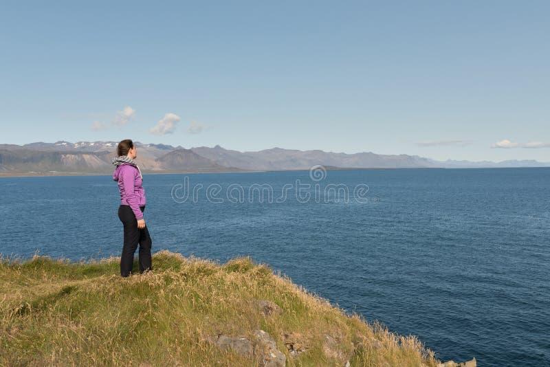 Ontspannen vrouw die van zon, vrijheid en het leven genieten een mooi strand in IJsland royalty-vrije stock afbeelding
