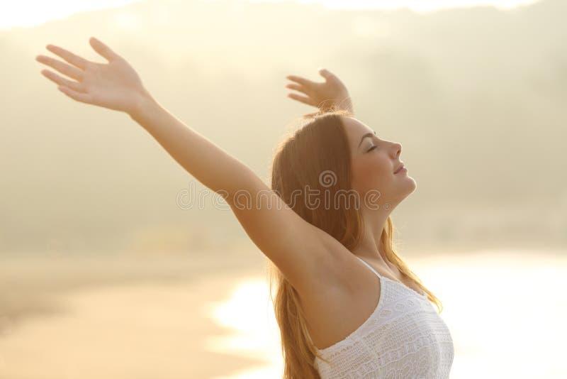 Ontspannen vrouw die verse lucht ademen die wapens opheffen bij zonsopgang royalty-vrije stock afbeelding