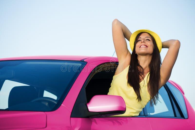 Ontspannen vrouw in roze auto op de vakantie van de wegreis stock fotografie