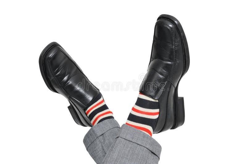 Ontspannen zakenman die zijn voeten kruisen stock afbeelding