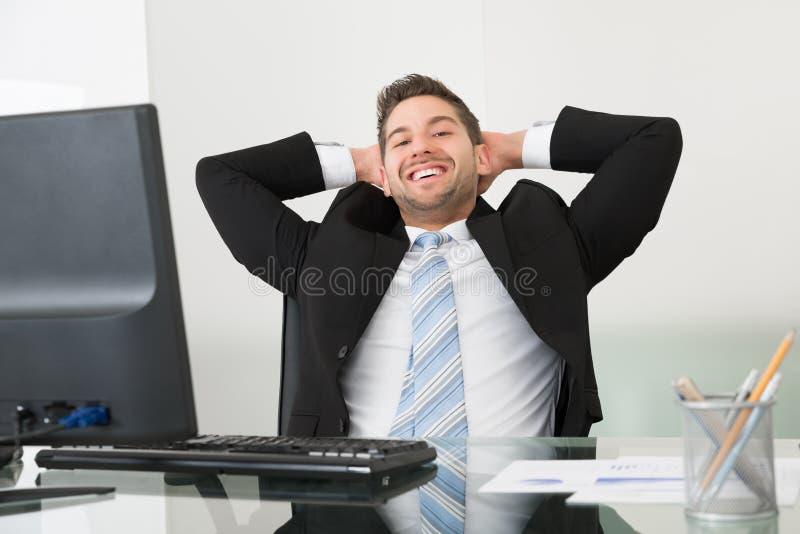 Ontspannen zakenman met handen achter hoofd bij bureau royalty-vrije stock foto's